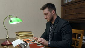 Focused journalist typing an article on typewriter sitting at the desk with green lamp. Professional shot on Lumix GH4 in 4K resolution. You can use it e.g. in stock footage