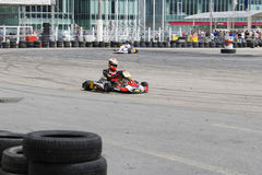 Focused kart racing driver on circuit with tire wall royalty free stock image