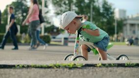Focused kid making first try on bike. Cute boy riding bike in amusement park