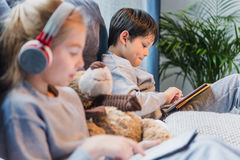 Focused little boy and girl in headphones using digital tablets. Side view of focused little boy and girl in headphones using digital tablets royalty free stock photography