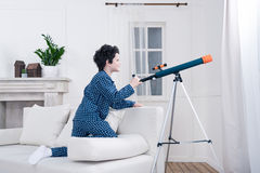 Focused little boy looking through telescope Stock Images