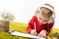 Focused little child drawing with color pencils and listening music on green soft carpet. Isolated on white royalty free stock photography