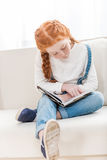 Focused little girl reading book while sitting on sofa at home Stock Images