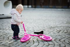 Focused little girl to ride balance bike outdoors, cute small baby trying bicycle. Little girl to ride balance bike outdoors, cute small baby trying bicycle Royalty Free Stock Image