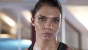 Focused look of a beautiful woman after a hard training. Sweaty face.