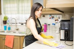 Busy young maid cleaning kitchen platform. Focused maid wiping kitchen platform with napkin wearing yellow rubber gloves and black apron Stock Photo