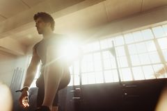 Focused male athlete at cross training gym. Focused male athlete standing at cross training gym.  Fitness man before starting his workout at health center Royalty Free Stock Photo