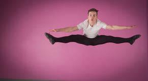 Focused male ballet dancer leaping doing the splits. In the dance studio Royalty Free Stock Photos