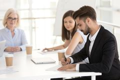 Focused male employee sign work contract at business meeting. Focused Caucasian millennial employee sign work contract at business meeting with female employers stock image