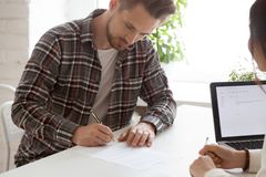 Focused male employee signing work contract after successful int stock images