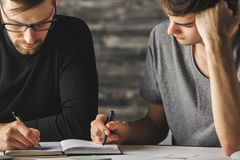 Focused males doing paperwork. Portrait of focused young males doing paperwork in modern office. Teamwork concept Royalty Free Stock Photography