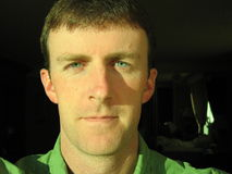 Focused Man. Close up of a man with blue eyes, brown hair and green shirt with a hotel room behind him Royalty Free Stock Images