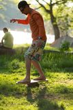 Focused man barefoot is training on balance board. On green meadow next to the river on sunny evening Royalty Free Stock Photography