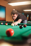 Focused man beats a billiard ball. Royalty Free Stock Photos