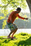 Focused man in cap is training on the balance board. On a green meadow next to river on sunny evening. Back light Royalty Free Stock Images