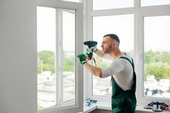 Man is doing window repair. Focused man is doing window repair, fixing and adjustment. Worker of handyman agency, home maintenance concept royalty free stock photography