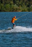 Focused man is engaged in wakeboarding. Focused man, in orange shirt and helmet, is engaged in wakeboarding in cable park on a sunny day. Active vacation in Royalty Free Stock Photo