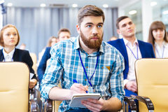 Focused man listening and making notes on presentation Stock Image