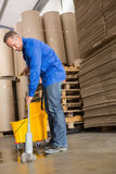 Focused man moping warehouse floor. Portrait of focused man moping warehouse floor Stock Image