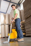 Focused man moping warehouse floor. Portrait of focused man moping warehouse floor Stock Photos