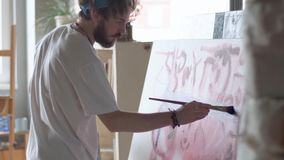 Painter Works at the Easel. Focused man painting a picture at the easel, wearing white t-shirt and blue bandana as working in spacious light studio, concept of stock video footage