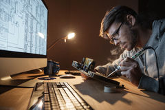 Focused man repairing motheboard with soldering iron Royalty Free Stock Photo