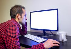 Focused Man Stares at Office Computer on Wooden Black Desk Mockup. Dotted Red Shirt, LCD Screen, Keyboard, Mouse, White Mug. Copy royalty free stock image