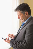 Focused man texting on his mobile phone Stock Images