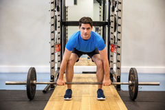 Focused man about to lift a barbell Stock Images
