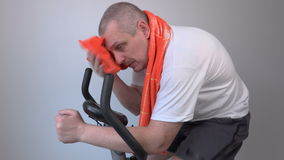 Focused man with a towel on exercise bike stock video footage