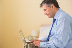 Focused man using a laptop sitting on a bed Stock Photos