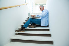 Focused man using laptop on steps Stock Photo