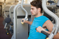 Focused man using weights machine for arms Stock Photos