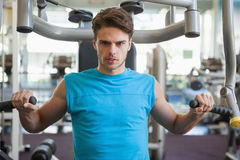 Focused man using weights machine for arms Royalty Free Stock Photo