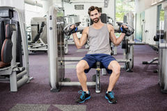 Focused man using weights machine for arms. At the gym Royalty Free Stock Images