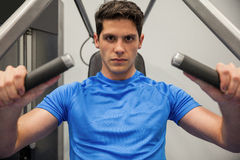 Focused man using the weights machine Stock Images