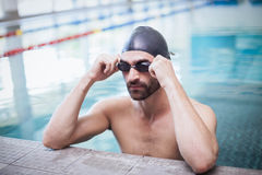 Focused man wearing swim cap and goggles Stock Photos