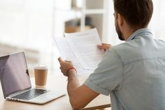 Focused man working at laptop reading paperwork documents royalty free stock images