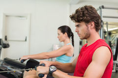 Focused man working out on the rowing machine Royalty Free Stock Photo