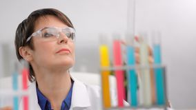 Focused mature female chemist in safety glasses mixing colorful reagent tube making researching. Focused mature female chemist in safety glasses mixing colorful stock footage