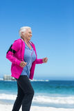 Focused mature woman running and listening to music Stock Photography