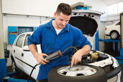 Focused mechanic inflating the tire Stock Photography
