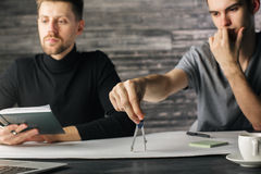 Focused men doing paperwork. Portrait of focused young men doing paperwork in modern office. Teamwork concept Royalty Free Stock Photos