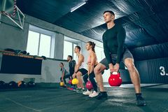 The strong young fitness men and women in sportswear doing exercises at gym. The focused and motivated strong young fitness men and women in sportswear doing royalty free stock photos