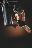 Focused muay thai fighter practicing kick on punching bag Royalty Free Stock Photos