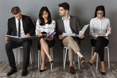 Focused multicultural business people with folders and notebooks waiting. For job interview royalty free stock photo