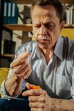 Focused old upset man holding an orange container with pills. Unpleasant man looking. Focused old upset man holding an orange container with pills and deeply royalty free stock images