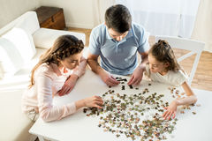 Focused parents and daughter playing with puzzles Royalty Free Stock Images