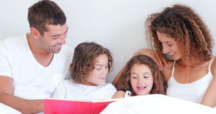 Focused parents reading tale to their children stock video footage
