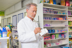 Focused pharmacist writing on box of medicine Royalty Free Stock Image